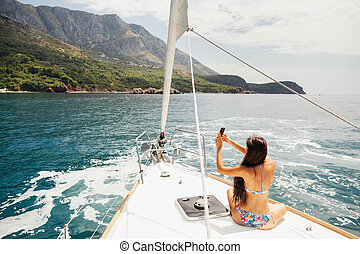 girl yachting with smartphone photograph cruise travel with...