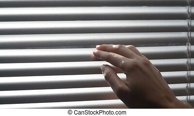 Woman looking through the blinds of the window to the...