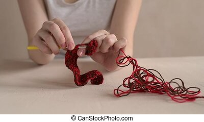 Woman crocheting with red and brown yarn HD