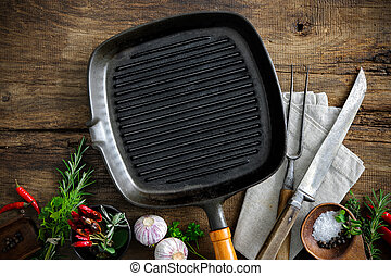 Empty grill pan with seasonings and meat fork on wooden...