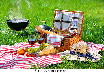 Picnic on a meadow - Picnic setting with red wine glasses,...