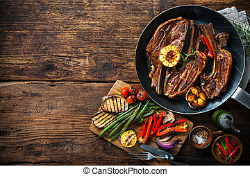 Roasted lamb meat with vegetables on grill pan on wooden...