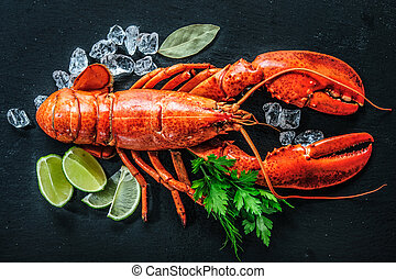 Top view of whole red lobster with ice and lime on a black...