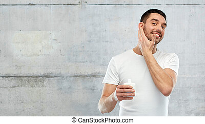 happy young man applying cream or lotion to face