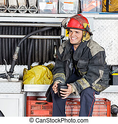 Happy Fireman Holding Coffee Mug In Truck At Fire Station -...