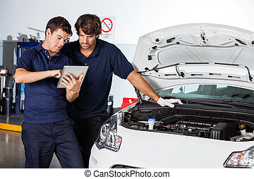 Mechanics Using Tablet Computer By Damaged Car - Male...