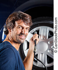 Mechanic Refilling Car Tire - side view portrait of male...