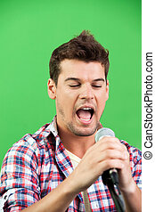 Male Singer Performing Against Green Wall
