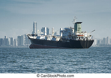 View of a large cargo ship anchored and the city skyline at...