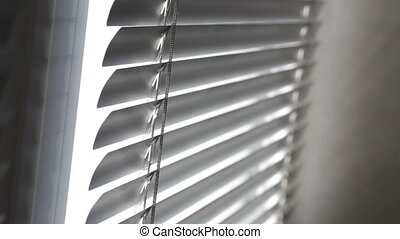 Sunlight coming through venetian blinds by the window.