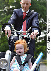 Business men riding his young child to creche - Business men...