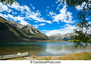 Canoe by lake - Touring canoe on a mountain lake shoreline
