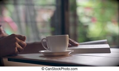 Man hands read a book and drinking coffee nature background...