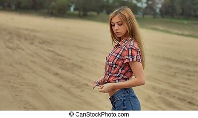 sexy girl in jeans and shirt sitting on sand in slow motion...