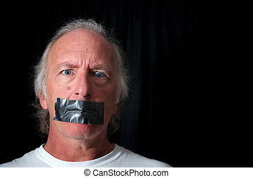 wide eyed man with duct taped mouth - Studio portrait of an...