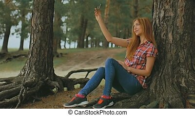 girl doing selfie on phone smartphone sitting in tree...