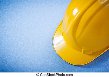 Yellow safety helmet on blue surface construction concept