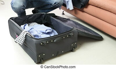 trip, luggage and people concept - man packing clothes into...