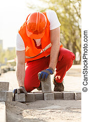 Worker with cobbles - Image of worker with cobbles building...