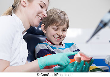 Friendly child dentist trying to cheer up her little patient...