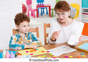 Speech therapist and little patient - Little boy during...