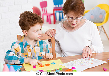 Play-centered learning - Young boy learning new words...
