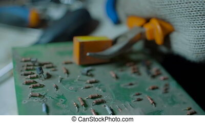 Demounting the Electronic Circuit Board Apart with Pliers....