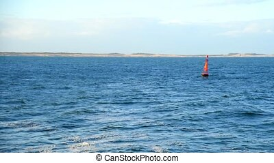 Red buoy floating in sea water