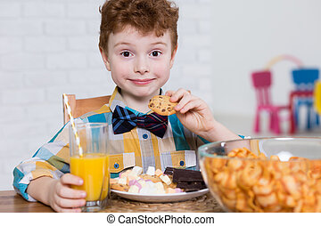 Little glutton and plate full of sweets - Happy little boy...