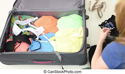 Girl collects clothes into a suitcase puts clothes