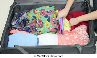 Girl collects clothes into a suitcase. puts clothes