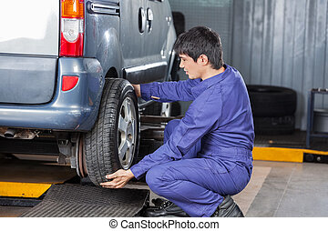 Mechanic Replacing Car Tire At Repair Shop - Side view of...