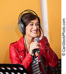 Woman Singing While Looking Away In Recording Studio -...