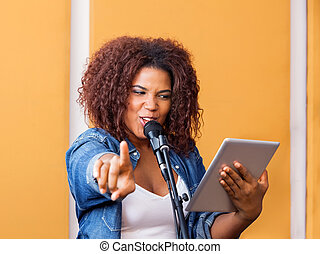 Female Singer Pointing While Holding Digital Tablet
