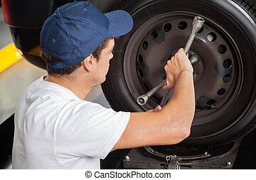 Mechanic Fixing Car Tire - Side view of male mechanic fixing...