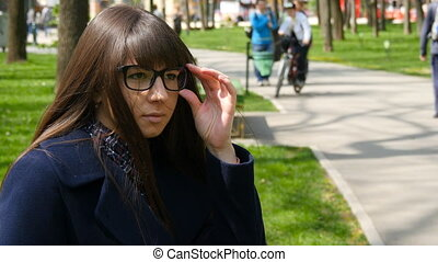 Young girl wearing glasses and waiting meet in park. Attractive woman sitting on bench enjoying life outdoors in spring