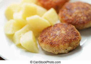 prepared fried fish cakes with boiled potatoes, shallow...