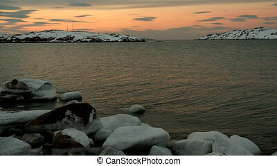 Sunset, North Sea, rocks in the snow, light wave
