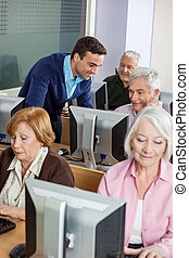 Teacher Assisting Senior Students In Computer Class
