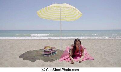Cute woman laying down on beach blanket - Single cute woman...