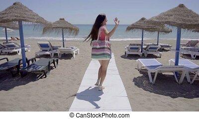 Cute woman walking on boardwalk to beach - Cute single...