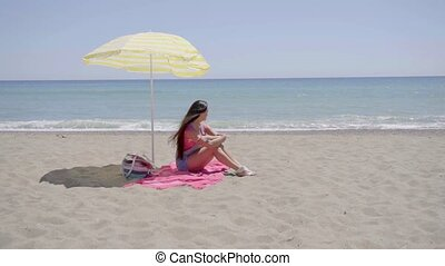 Lone woman sitting on beach under umbrella - Lone woman...