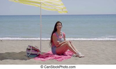 Pretty woman on blanket under beach umbrella - Pretty...