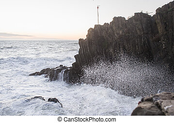 Waves breaking over cliff in Ligurian sea during a stormy...