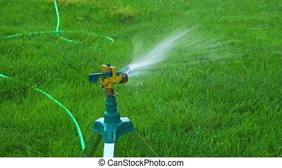 Garden working motion side view. - Garden sprinkler working...