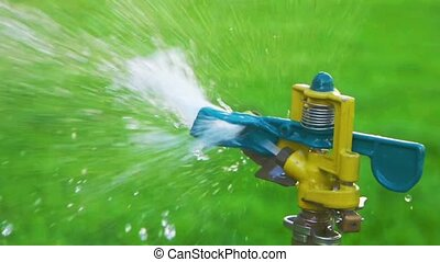 Garden sprinkler slow motion side view - Garden sprinkler...