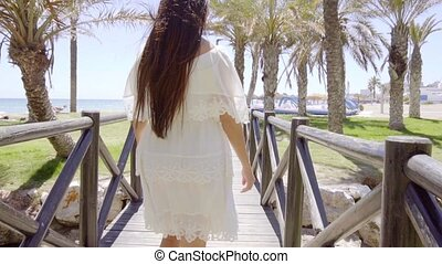 Woman looking back while walking to beach - Young pretty...