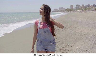 Pretty woman walking next to beach