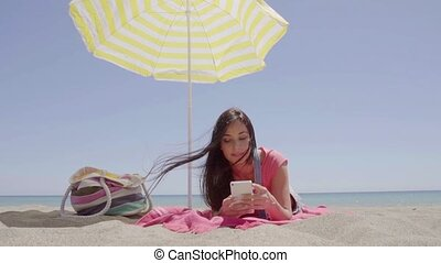 Ground level view of woman using phone at beach - Ground...