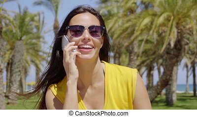 Pretty young woman in sunglasses on her mobile - Pretty...